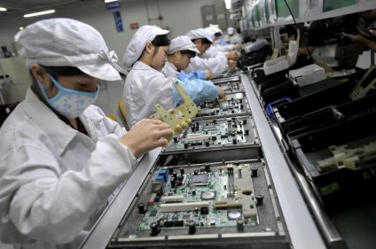 In a picture taken on May 26, 2010 Chinese workers assemble electronic components at the Taiwanese technology giant Foxconn's factory in Shenzhen, in the southern Guangzhou province. Foxconn on June 2 confirmed the death of another employee but denied he died of exhaustion following a spate of suicides at its Chinese plants. CHINA OUT AFP PHOTO (Photo credit should read AFP/AFP/Getty Images)
